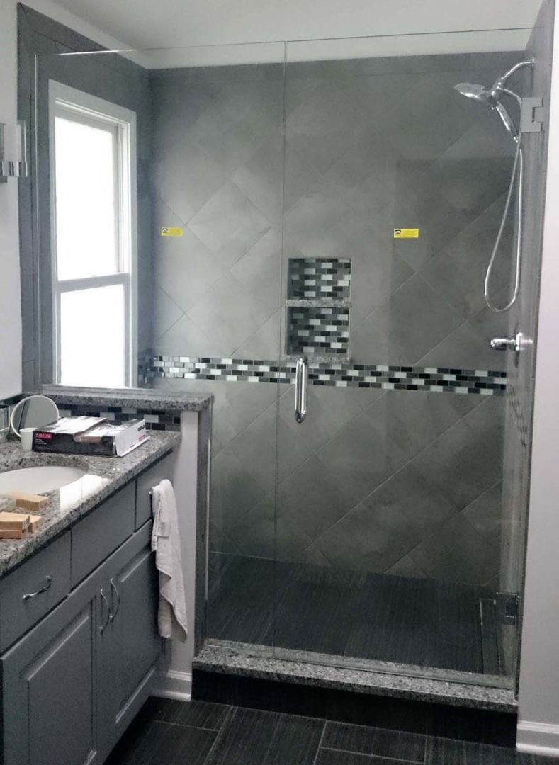 custom glass door and panel shower enclosure on knee wall with u channel