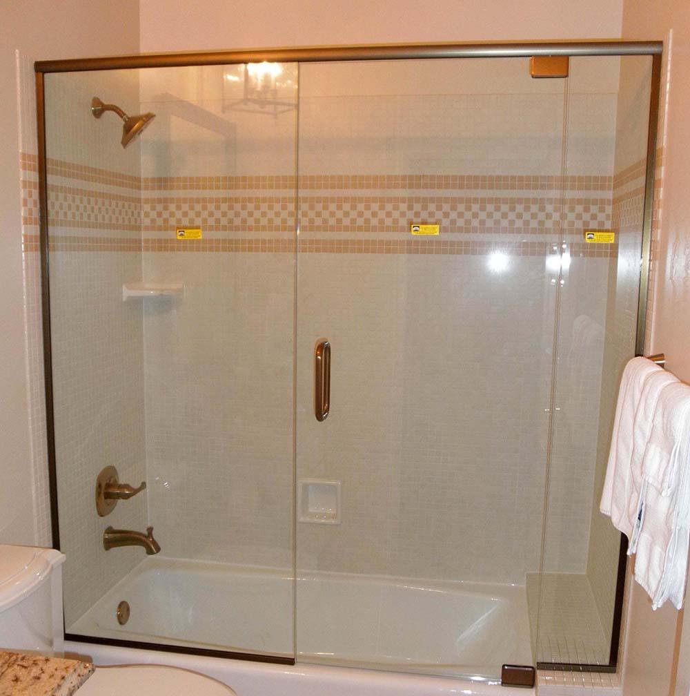 custom glass shower enclosure on bathtub with header bar with u channel