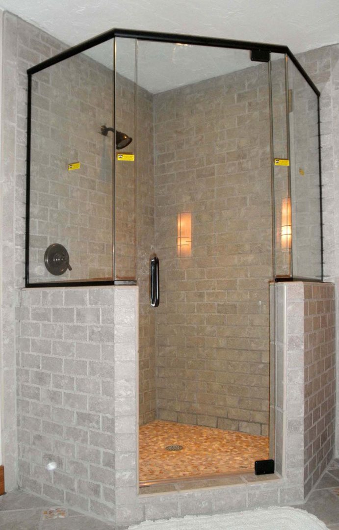 custom glass neo-angle shower enclosure on knee wall with header bar with u channel