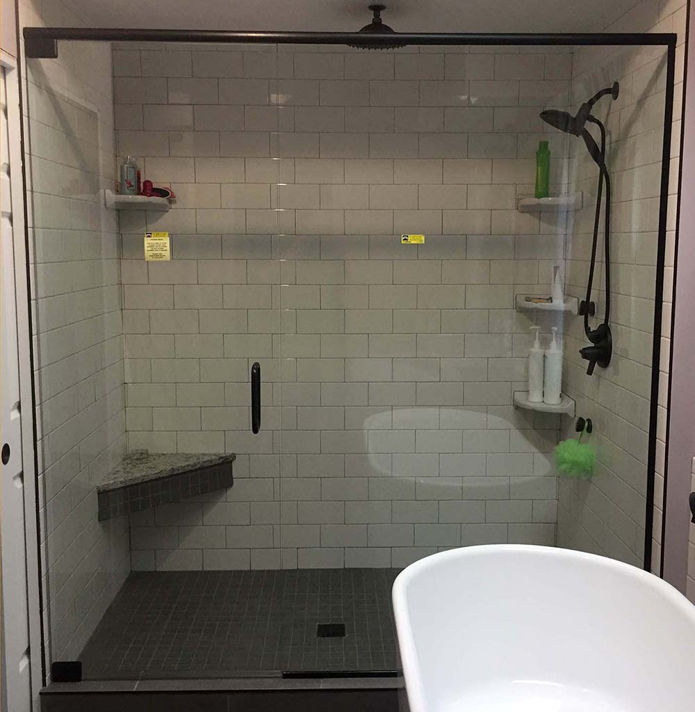 custom glass door and panel shower enclosure with header bar with u channel