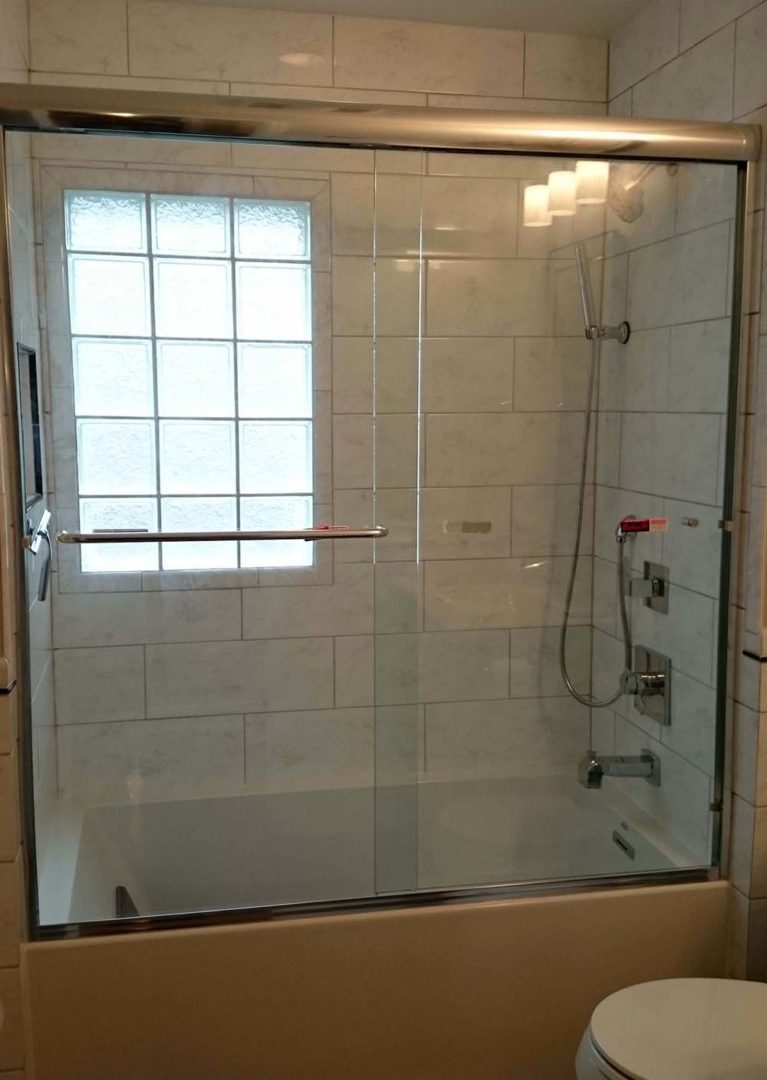 custom glass bypass shower enclosure on bathtub