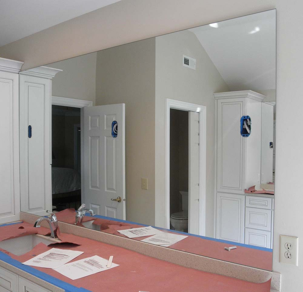 custom polished mirror with cutouts above vanity
